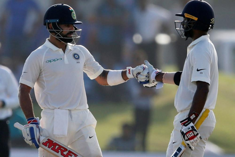 India's captain Virat Kohli (L) and Abhinav Mukund celebrate their partnership during the first cricket Test match against Sri Lanka in Galle Friday. — Reuters