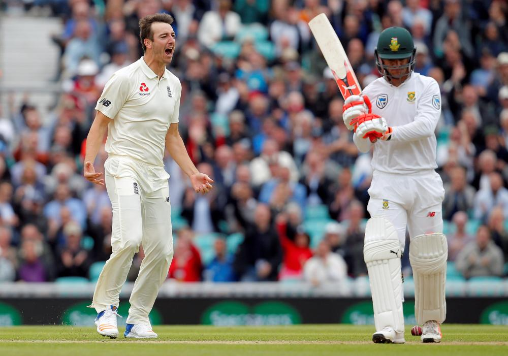 England's Toby Roland-Jones celebrates the wicket of South Africa's Heino Kuhn during their third cricket Test match in London Friday. — Reuters