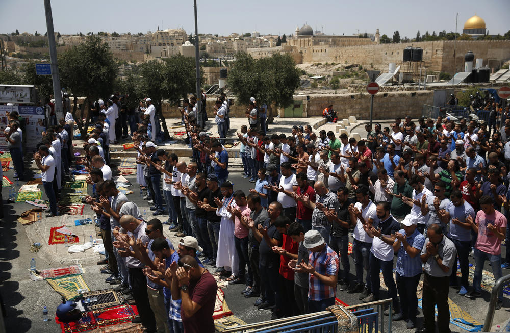 Palestinians pray outside Al-Aqsa Mosque in occupied Jerusalem's Old City, Friday. — AP