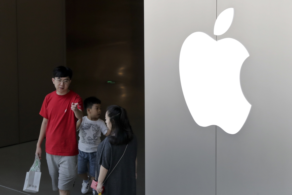 A Chinese family walks out of an Apple store in Beijing, Sunday. China appears to have succeeded in eliminating software programs that enable its people to view an uncensored Internet. Companies that let people avoid the government filters said Saturday their programs have been removed from Apple's app store in China. — AP