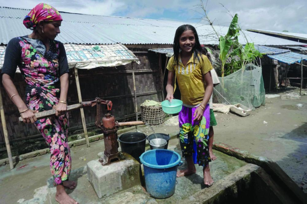 Muslim girls carry water in Da Paing IDP camp near Sittwe town in Rakhine state. Deadly sectarian riots in 2012 drove more than 100,000 Rohingya into the camps in Rakhine State, where they live in ramshackle homes and are deprived of adequate food, schools and doctors. —  AFP