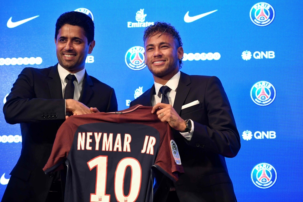 Brazilian superstar Neymar (R) poses with his jersey next to Paris Saint Germain's (PSG) president Nasser Al-Khelaifi during a press conference at the Parc des Princes stadium on Friday in Paris after agreeing a five-year contract following his world record 222 million euro ($260 million) transfer from Barcelona to PSG. — AFP