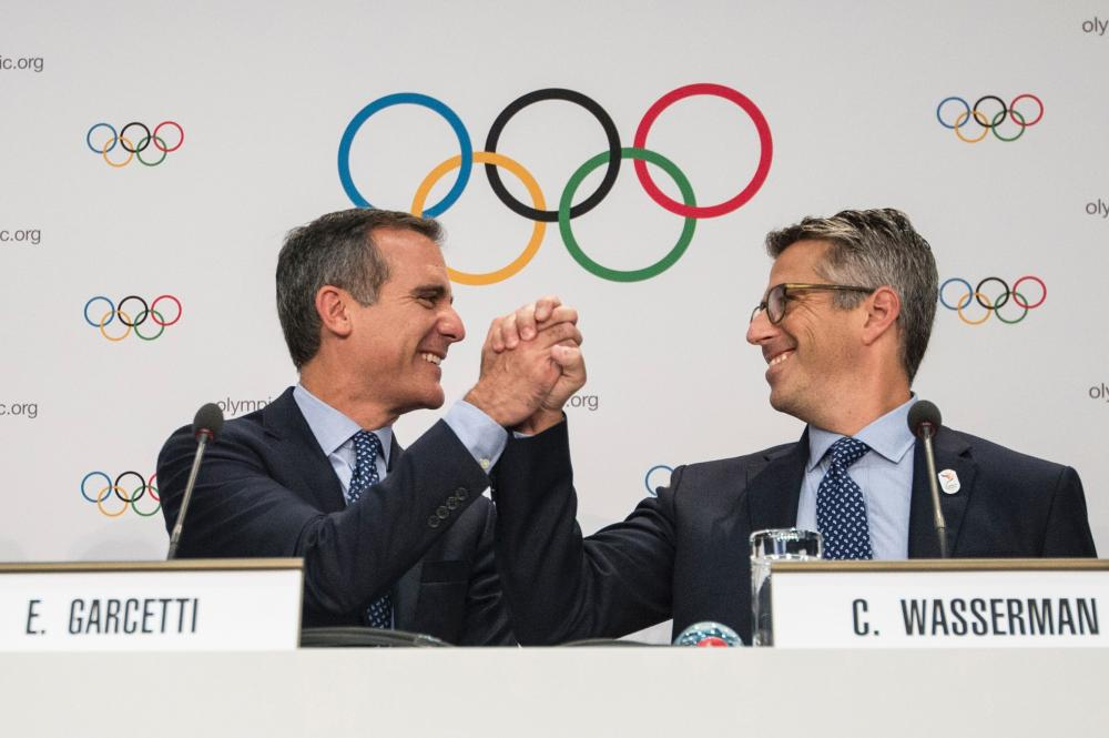 Los Angeles Mayor Eric Garcetti (L) shakes hands with LA 2024 Chaiman Casey Wasserman during a press conference after the Los Angeles 2024 bid presentation before members of the International Olympic Committee (IOC) on July 11, 2017 in Lausanne. — AFP