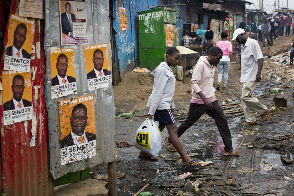 Kenyans walk past election posters in the Kibera slum in Nairobi, Kenya, on Monday. — AP