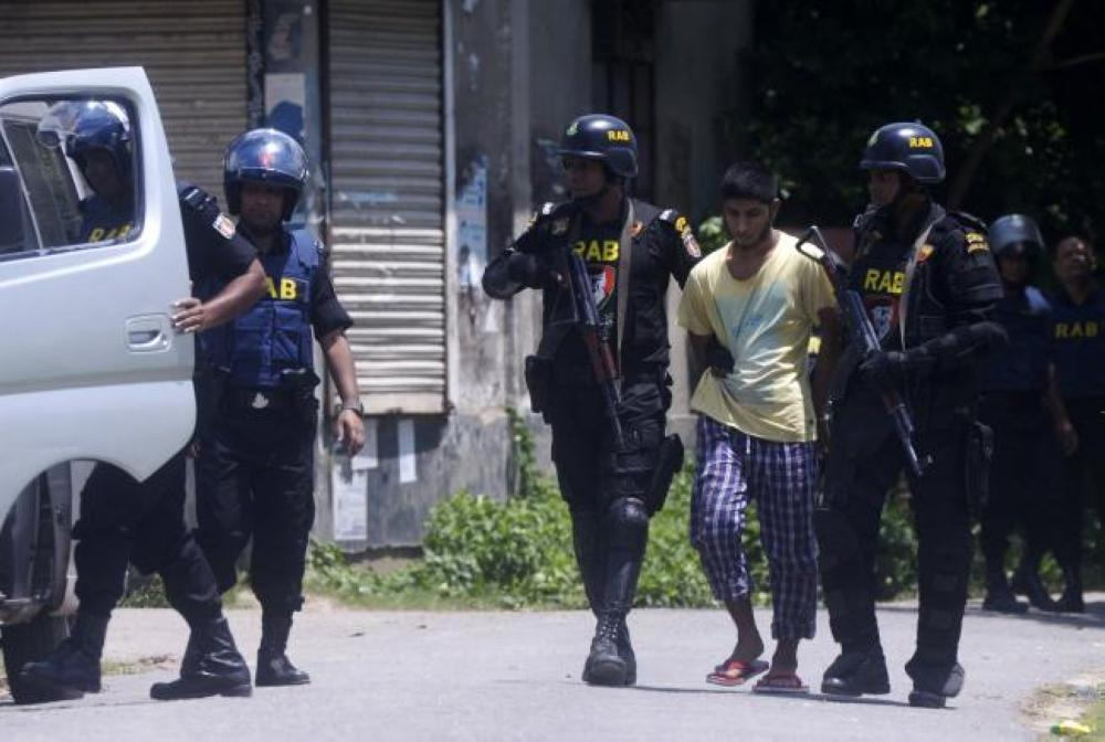 Bangladesh Rapid Action Battalion (RAB) personnel detain a suspected Islamist extremist after he surrendered in Ashulia, some 25 km from Dhaka, in this July 16, 2017 file photo. — AFP