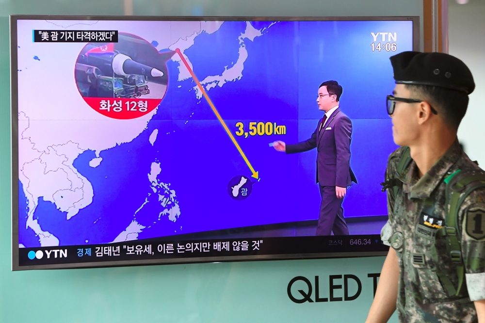 A South Korean soldier walks past a television screen showing a graphic of the distance between North Korea and Guam at a railway station in Seoul on Wednesday. — AFP
