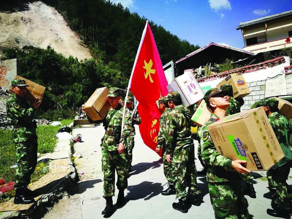 Chinese paramilitary police carry relief supplies on their way to an earthquake-stricken zone in Jiuzhaigou.