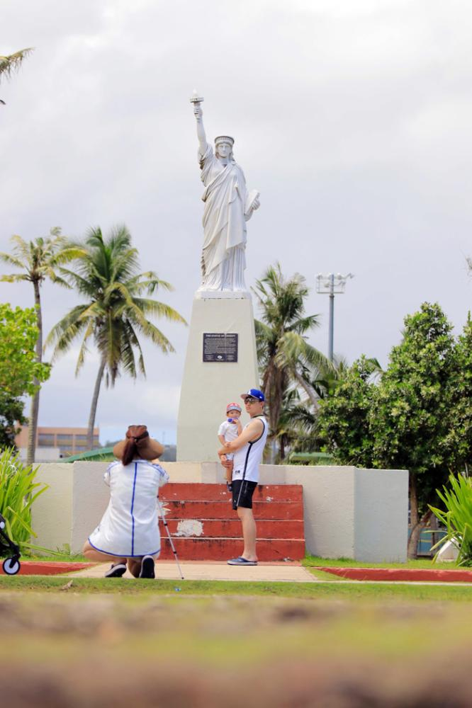 Tourists pose for photos in front of a miniature Statue of Liberty at Paseo de Susan Park in Agana near Hagatna on the island of Guam.