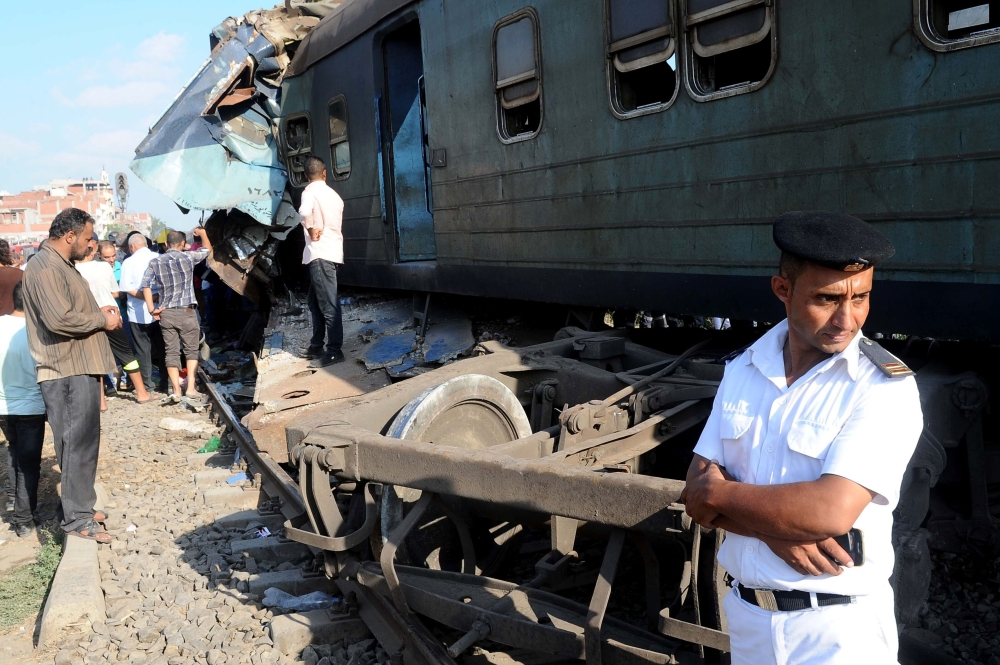 Egyptian security forces stand guard at the site of a train collision in the area of Khorshid, in Egypt's Mediterranean city of Alexandria, on Friday. — AFP