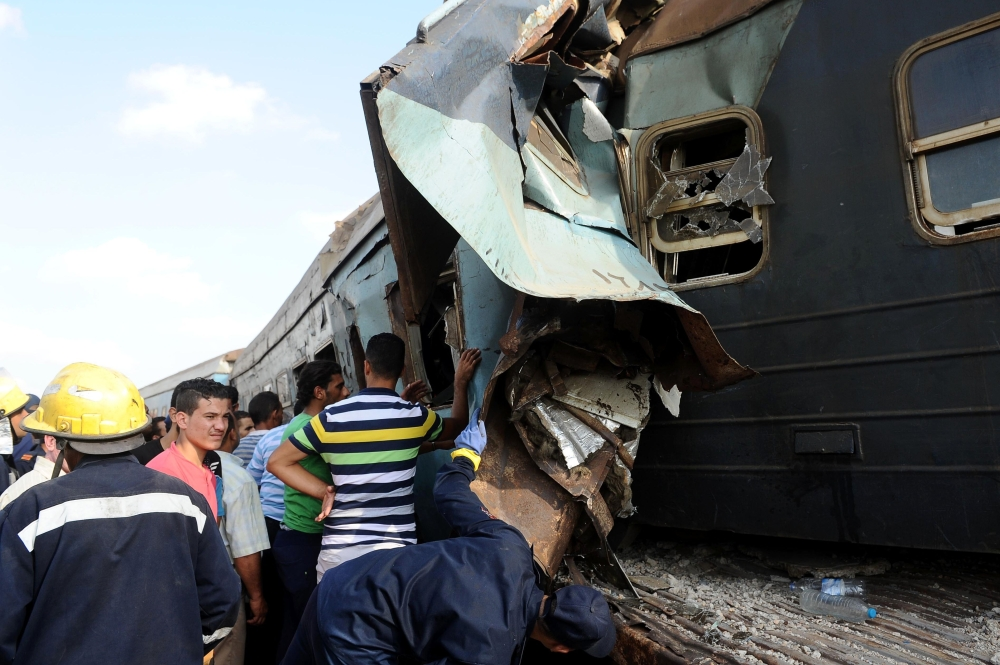People gather at the site of a train collision in the area of Khorshid, in Egypt's Mediterranean city of Alexandria, on Friday. — AFP