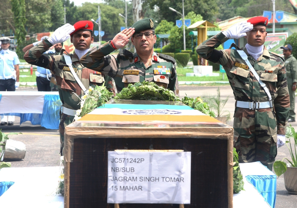 Indian army officers salute the coffin with the body of slain soldier Jagram Singh Tomar in Mendhar area of Poonch district, at an army garrison in Jammu, on Sunday.  AFP