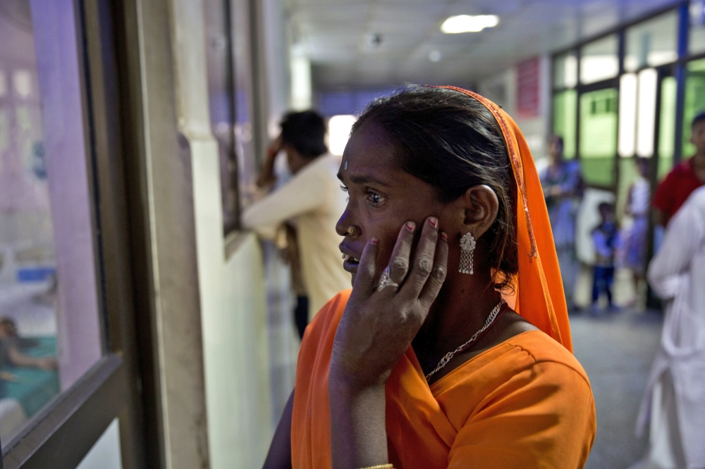 An Indian woman looks through the window glass of the emergency ward for a glimpse of her one and half year old grandson who is under treatment at the Baba Raghav Das Hospital where 35 children died in three days in Gorakhpur, Uttar Pradesh, India, on Sunday. — AP