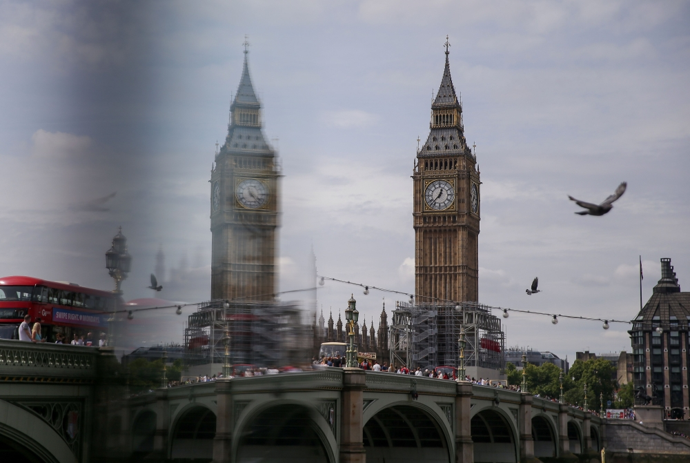 One of the four faces of the Great Clock of the Elizabeth Tower, commonly referred to as Big Ben, is reflected as it is pictured at the Houses of Parliamnet in central London on Monday. — AFP