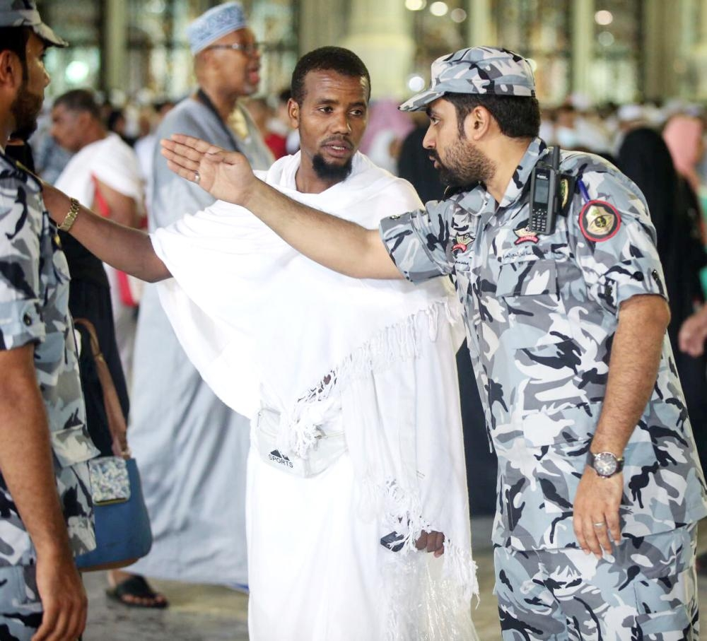 A security man helps a blind an aged pilgrim in Makkah, Monday. — Okaz photo