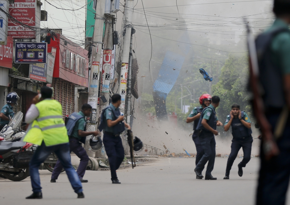 Bangladeshi policemen take cover following a blast as they try to flush out suspected radicals who have holed up in a building in Dhaka, Bangladesh, on Tuesday. — AP