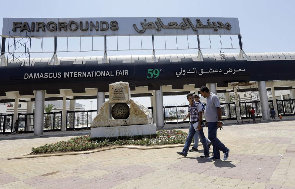 People walk past the Damascus International Fair in the Syrian capital countryside. The 10-day fair is scheduled to open on Aug. 17. — AFP