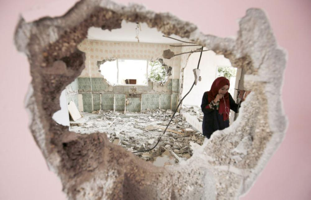 A woman checks the remains of the house of a Palestinian man after it was demolished by Israeli authorities in the West Bank village of Kobar, near Ramallah, Wednesday. — AFP