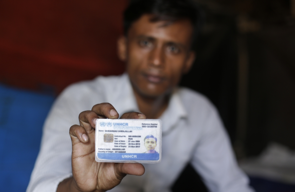 A Rohingya refugee Mohammad Sirajullah displays his UNHCR card as he sits inside his shanty at a temporary shelter in New Delhi on Wednesday. — AP