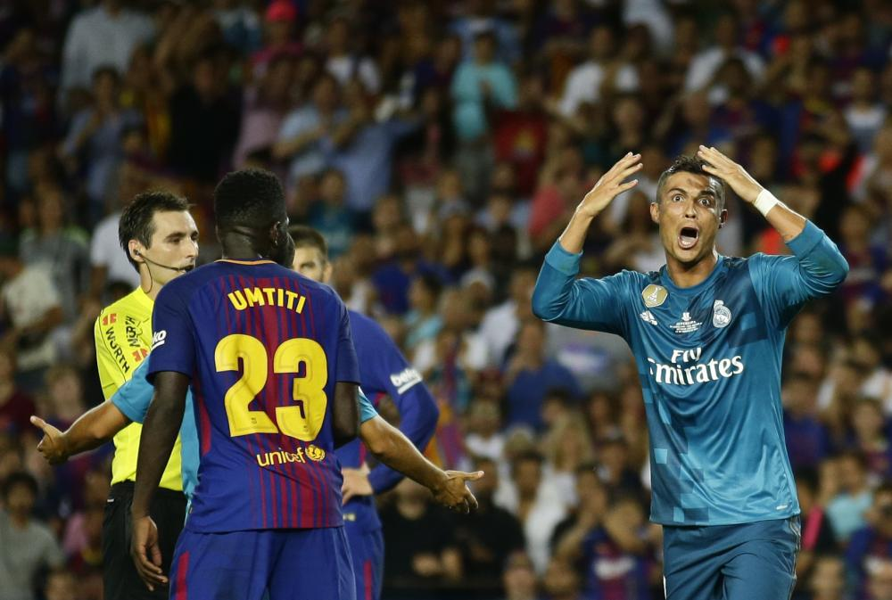 Real Madrid's Cristiano Ronaldo (R) reacts after Referee Ricardo de Burgos (L) shows a second yellow card during the Spanish Super Cup first leg match aginst FC Barcelona at the Camp Nou stadium in Barcelona Sunday. — AP