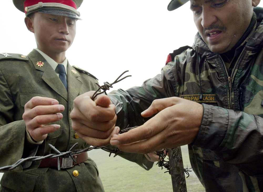 A Chinese soldier (left) and Indian soldier place a barbed wire fence following a meeting of military representatives at the Nathu La border crossing between India and China in India's northeastern Sikkim state last year. A border standoff between Chinese and Indian troops on a remote Himalayan plateau has heightened long-standing tensions while ensnaring a tiny kingdom, Bhutan, between the two nuclear-armed powers. — AFP