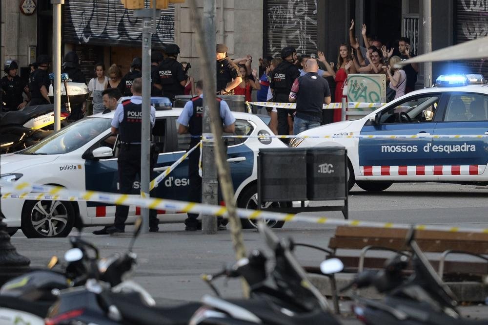 People leave a fastfood with hands up as asked by policemen after a van plowed into the crowd, killing two persons and injuring several others on the Rambla in Barcelona on Thursday. A driver deliberately rammed a van into a crowd on Barcelona's most popular street.  — AFP