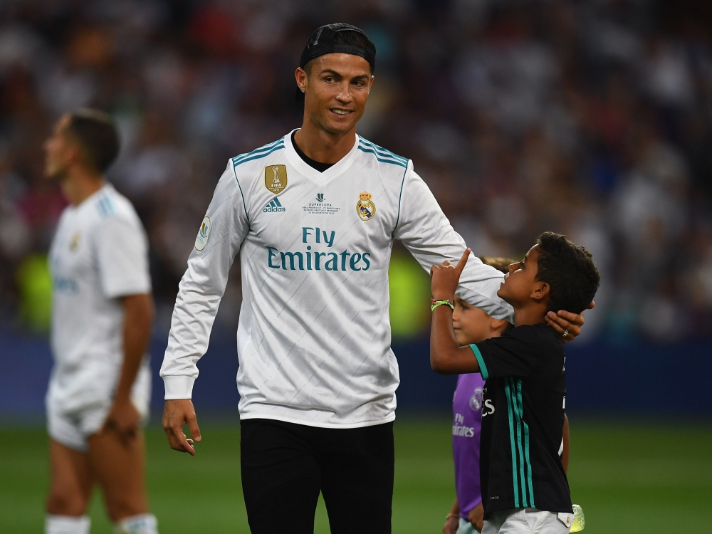 Real Madrid's Portuguese forward Cristiano Ronaldo (L) touches a boy's head as he celebrates their Supercup after winning the second leg of the Spanish Supercup football match against Barcelona at the Santiago Bernabeu stadium in Madrid, on Wednesday. — AFP