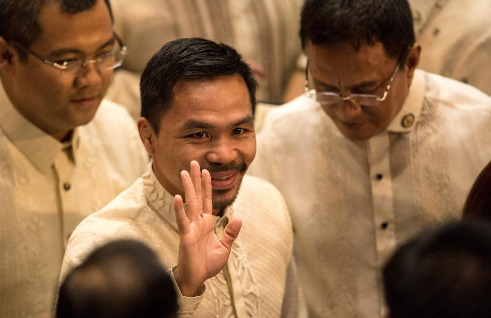 Philippine boxing icon and Senator Manny Pacquiao (C) arrives at the House of Representatives in Manila in this file photo, to attend Philippine President Rodrigo Duterte's second annual state of the nation address. — AFP