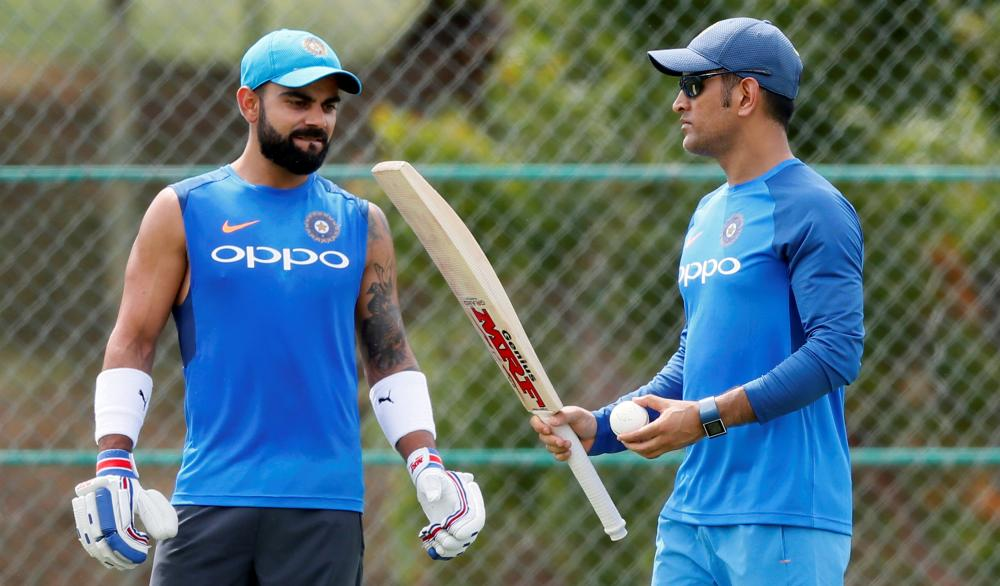 India's cricket captain Virat Kohli looks on as his teammate M.S. Dhoni weighs the bat during the Indian team practice session in Dambulla, Sri Lanka, on Friday. — Reuters