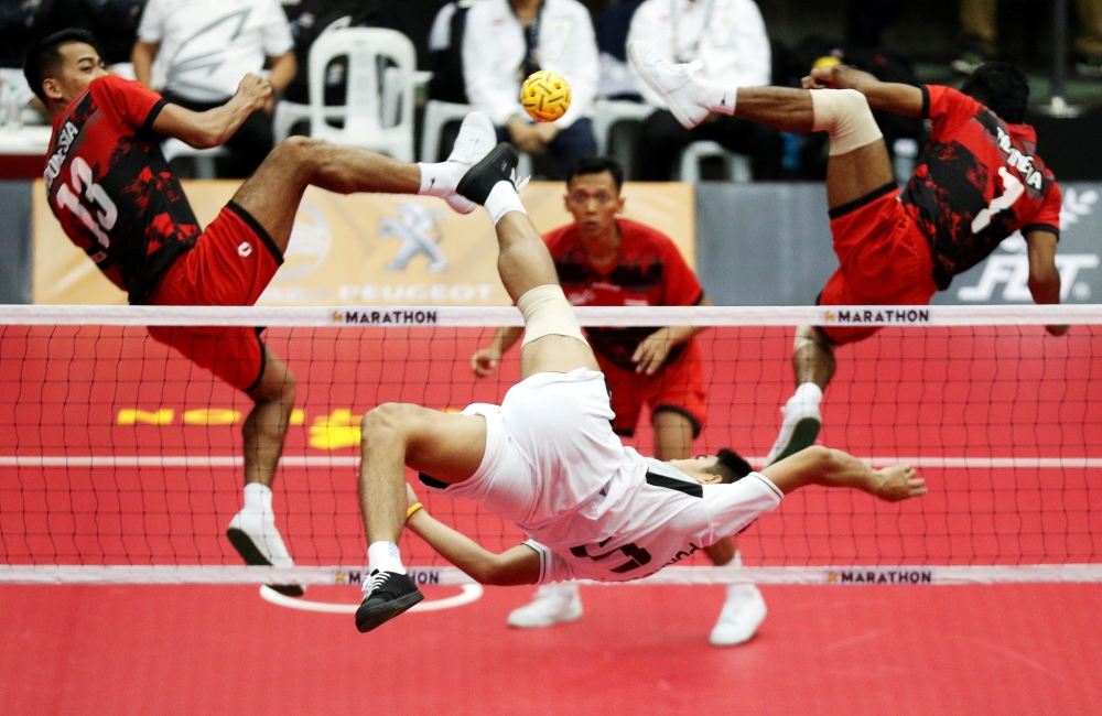 Thailand's Kritsanapong Nontakote takes a shot against Indonesia's  Saiful Rijal and Syamsul Hadi during the Men's Sepak Takraw Team Regu event on Friday at the Southeast Asian (SEA) Games in Kuala Lumpur. — Reuters
