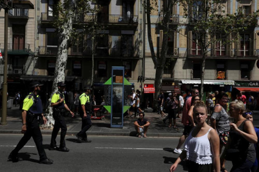 Police officers patrol a day after a van crashed into pedestrians at Las Ramblas in Barcelona