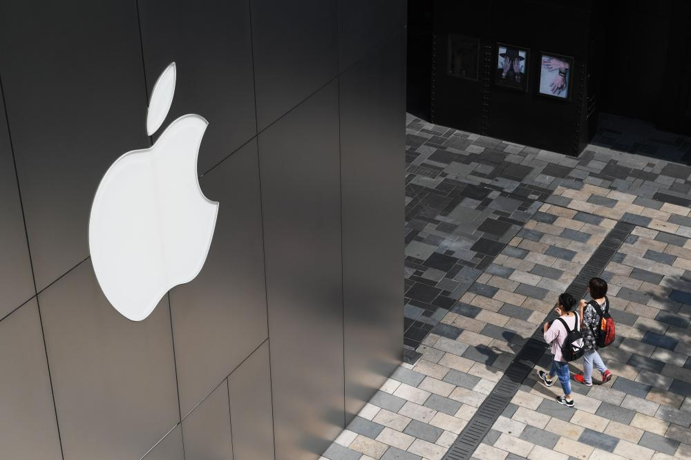 People walk past an Apple store in Beijing in this file photo. — AFP