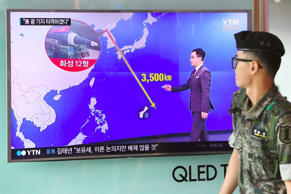 "A South Korean soldier walks past a television screen showing a graphic of the distance between North Korea and Guam at a railway station in Seoul. President Donald Trump issued an apocalyptic warning to North Korea, saying it faces ""fire and fury"" over its missile program, after US media reported Pyongyang has successfully miniaturized a nuclear warhead. — AFP"