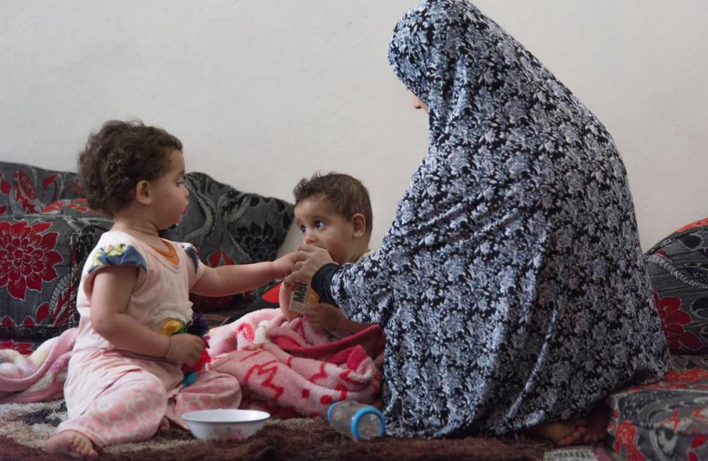 Swasan feeds her children at her home in East Amman, Jordan. The name has been changed to protect the identity. — Reuters