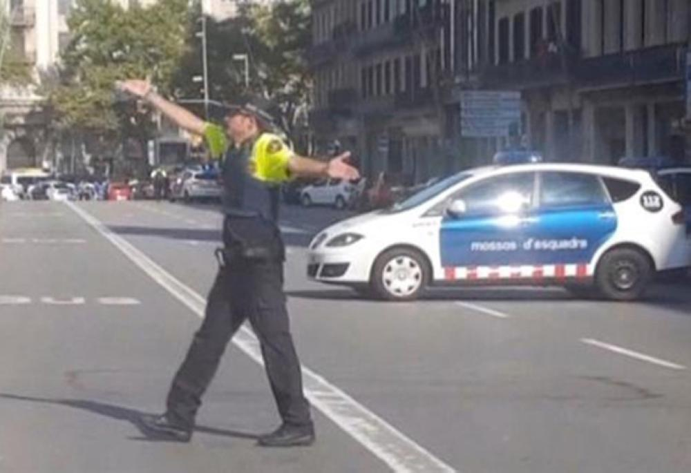 A police officer gesturing while walking across a road, after a van crashed into people in the center of Barcelona on Thursday. — Reuters