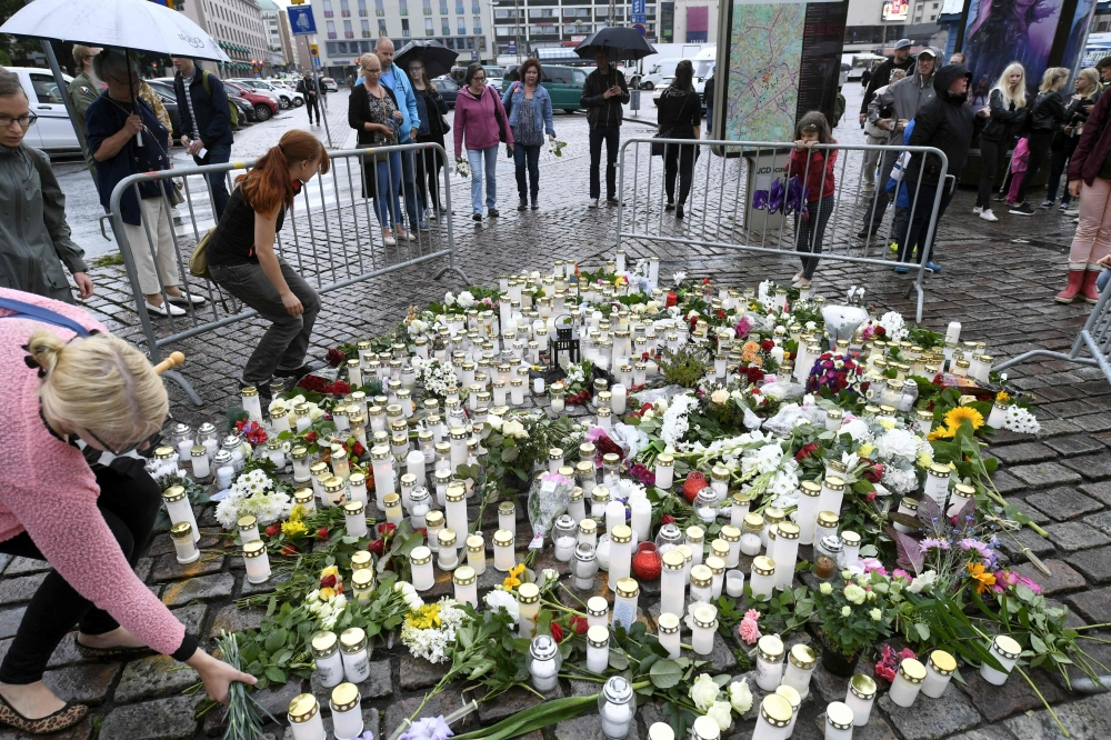 Peopole lay candles and flowers at the makeshift memorial for the victims of Friday's stabbings at the Turku Market Square, Finland, on Saturday. — AFP