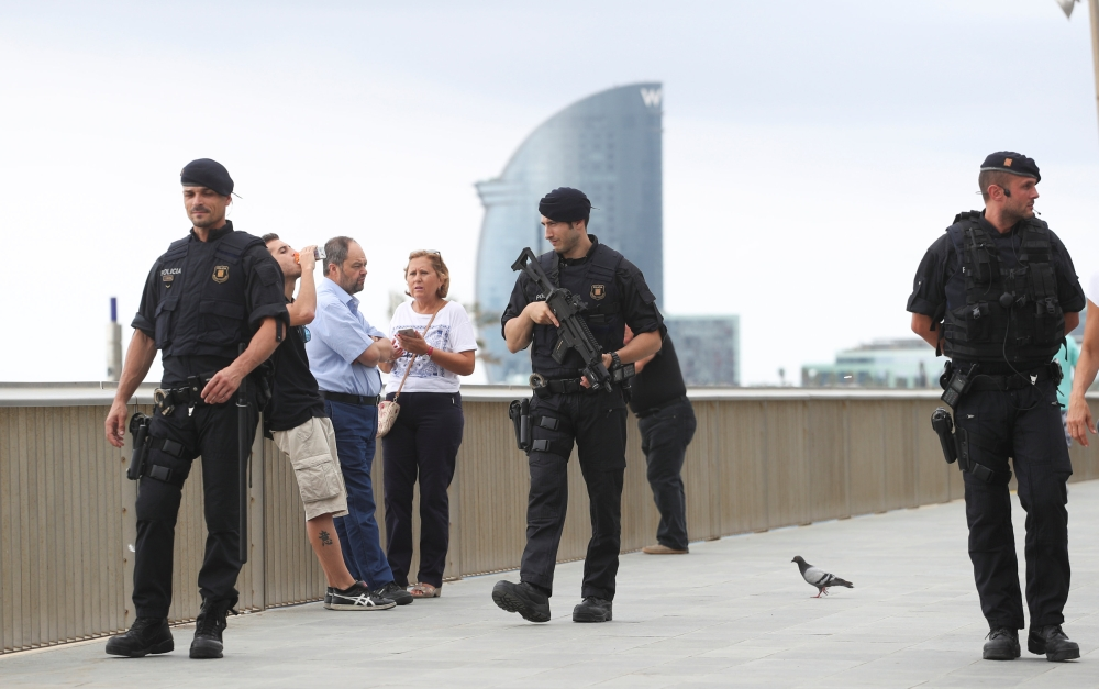 Armed Catalan Mossos d'Esquadra officers patrol along La Barceloneta beach in Barcelona, Spain, on Saturday. — Reuters