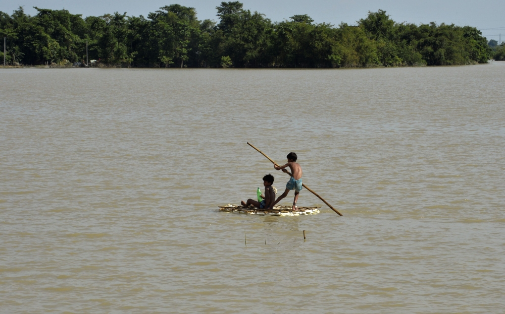 Indian children use a raft to travel over floodwaters in Araria in Bihar state on Saturday. — AFP
