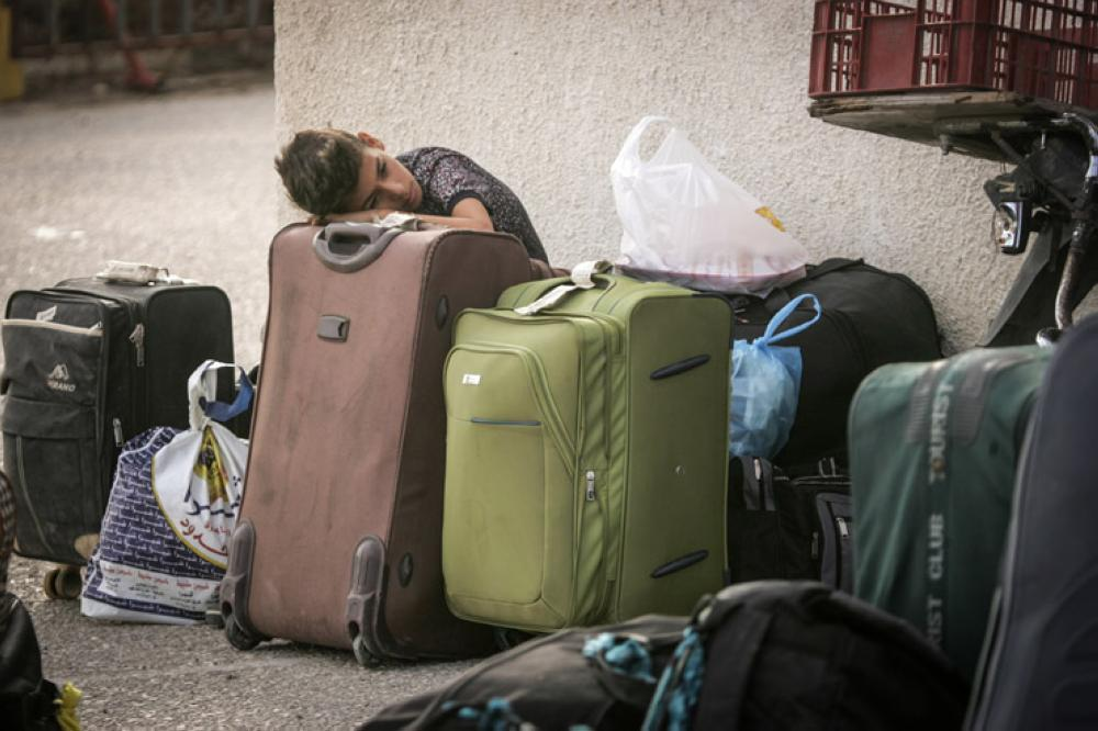 A Palestinian boy rests his head on his family's suitcases as he waits to pass through the Rafah border crossing into Egypt. Most of the Palestinians leaving Gaza through Egypt do so in order to reach third-country destinations. — Courtesy photo