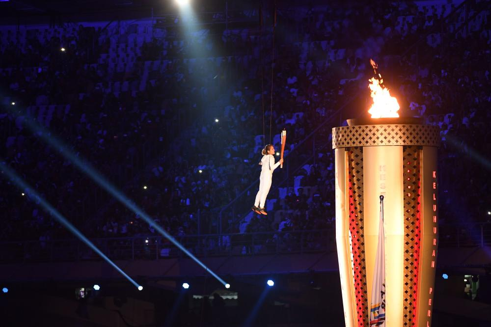 Malaysian athlete Nur Dhabitah ignites the torch during the opening ceremony of the 29th Southeast Asian Games (SEA Games) in Kuala Lumpur Saturday. — AFP