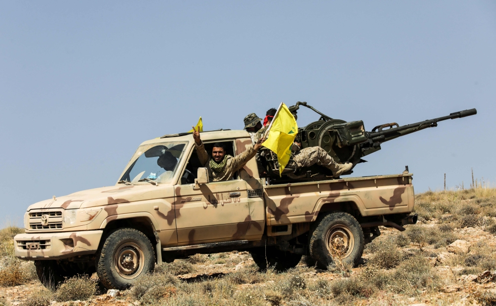 A picture taken during a tour guided by the Lebanese Shiite Hezbollah movement shows members of the group manning an anti-aircraft gun mounted on a pick-up truck in a mountainous area around the Lebanese town of Arsal along the border with Syria. — AFP