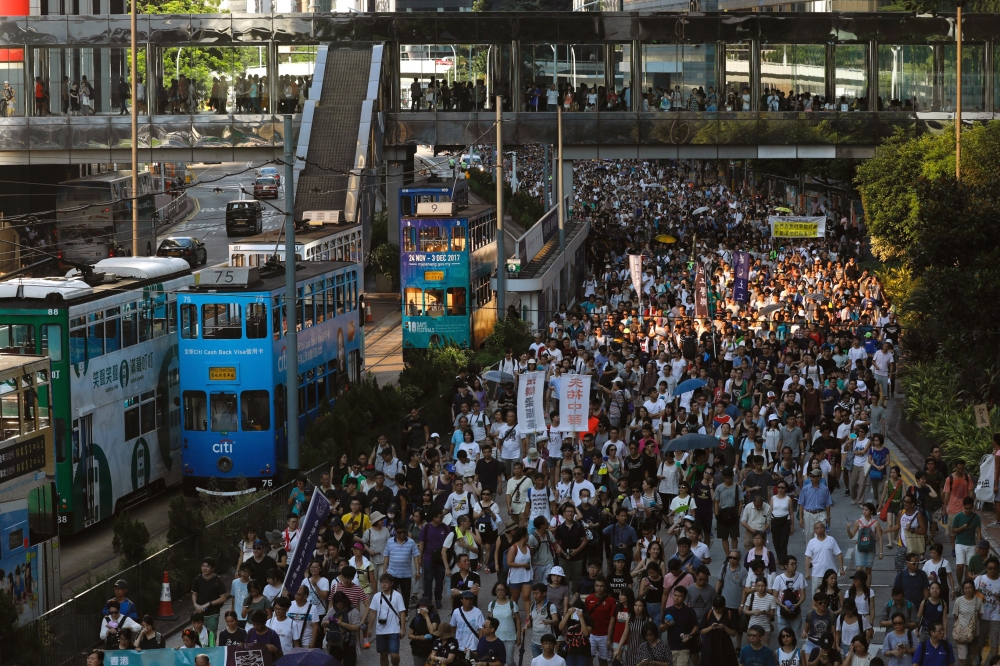 "Demonstrators march in protest of the jailing of student leaders Joshua Wong, Nathan Law and Alex Chow, who were imprisoned for their participation of the 2014 pro-democracy Umbrella Movement, also known as ""Occupy Central"" protests, in Hong Kong on Sunday. — Reuters"