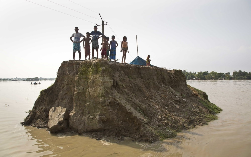 Flood-affected villagers wait for relief material on what's left of a road washed away by floodwaters in Morigaon district, east of Gauhati, northeastern state of Assam, in this Aug. 15, 2017 file photo. — AP