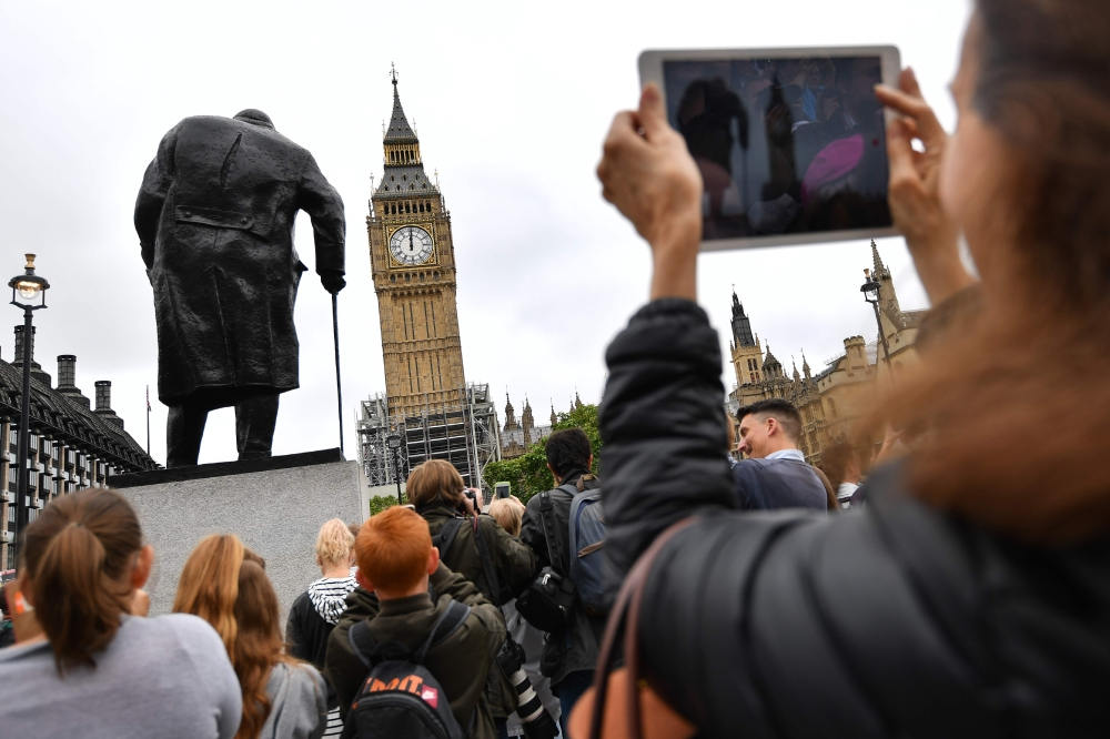 People photograph Elizabeth Tower (Big Ben) in Parliament Square at the Houses of Parliament in London on Monday. — AFP