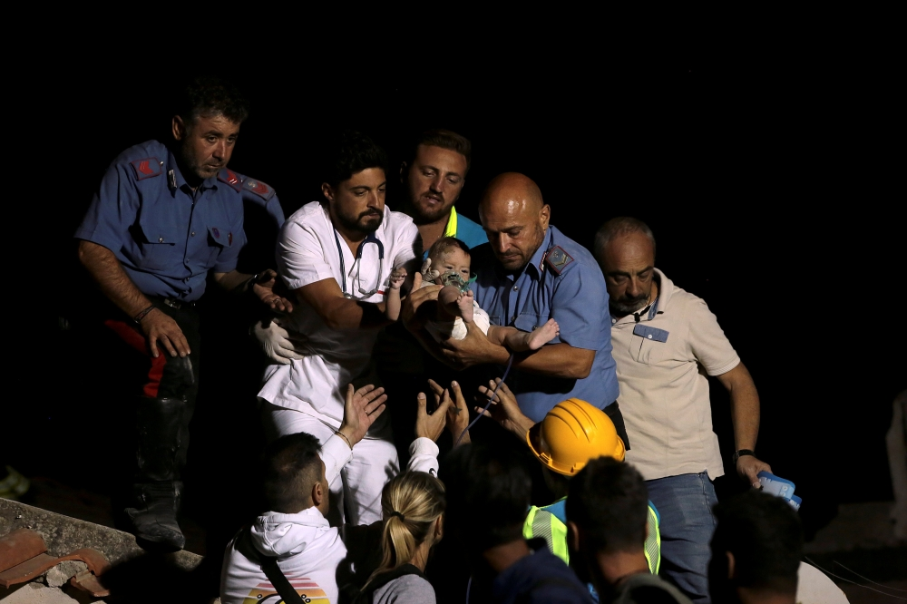 Italian Carabinieri police officer and a doctor carry a child after an earthquake hit the island of Ischia, off the coast of Naples, Italy, on Tuesday. — Reuters