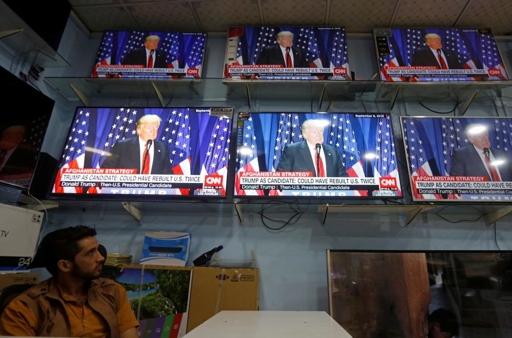 An Afghan man watches the TV broadcast of the US President Donald Trump's speech in Kabul on Tuesday. — Reuters