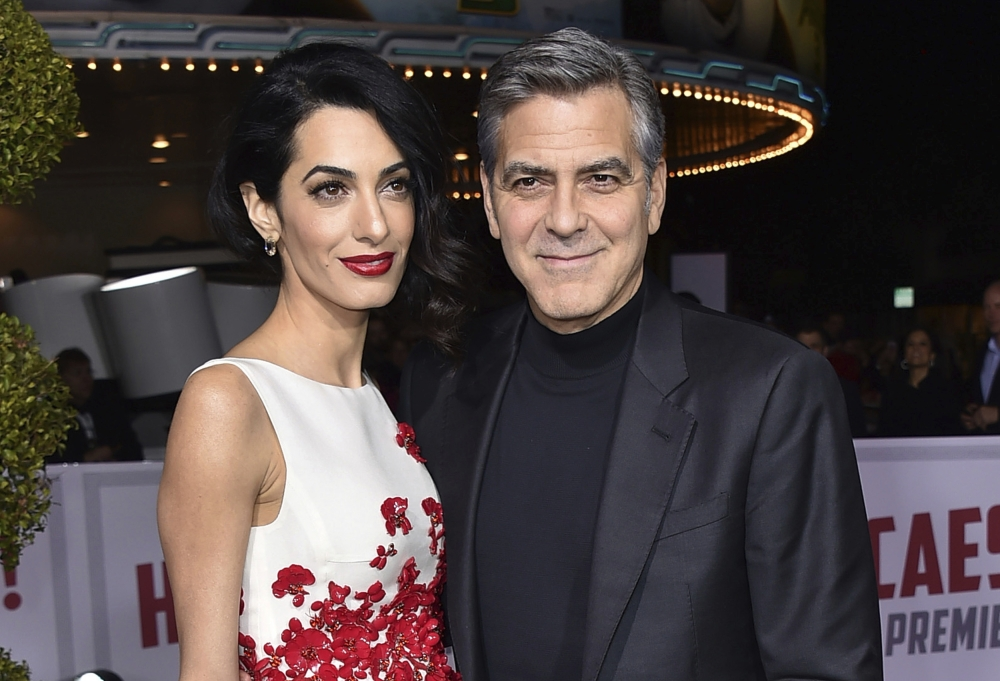 FILE - In this Feb. 1, 2016, file photo, Amal Clooney, left, and George Clooney arrive at the world premiere of