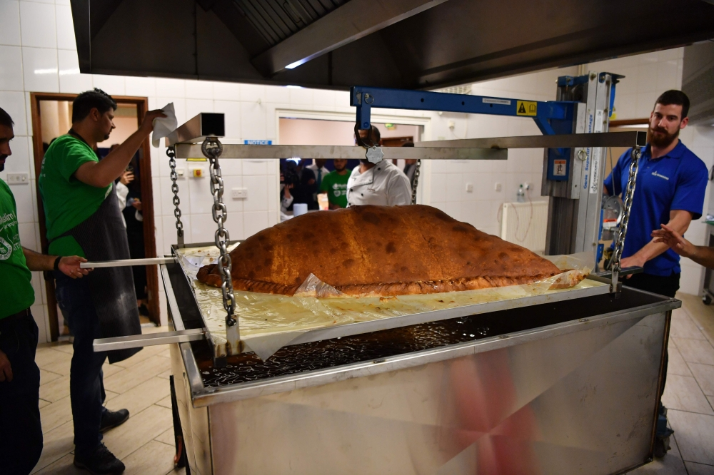 Muslim Aid staff and volunteers work as they attempt to construct and cook the world's largest samosa at the East London Mosque in London on Wednesday. - AFP