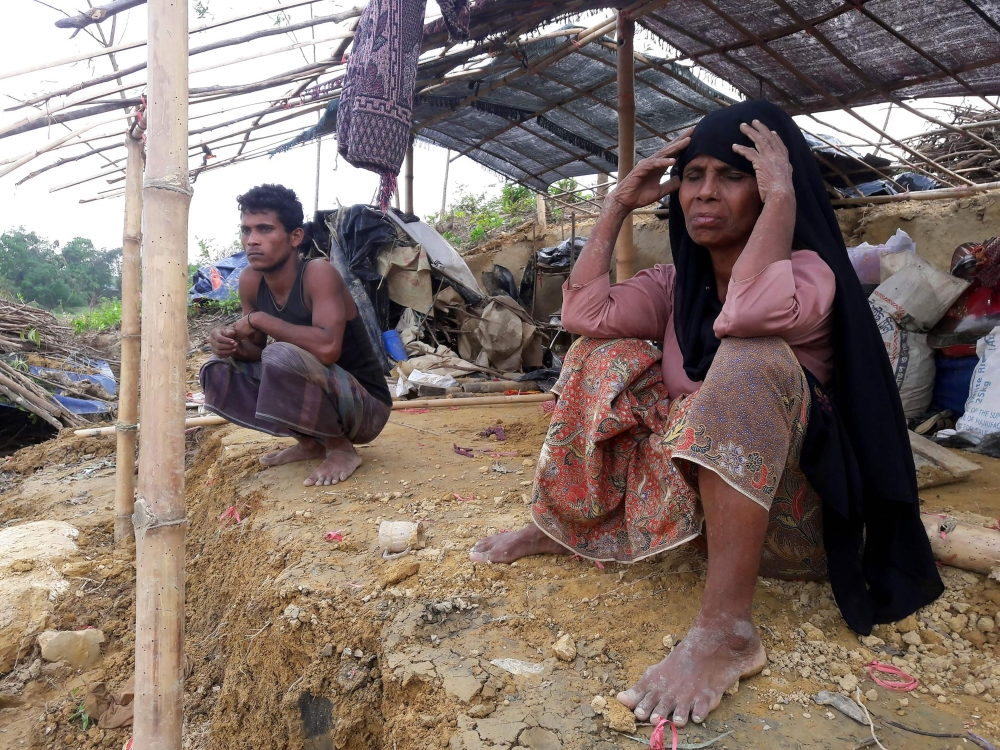 Rohingya refugees sit near a house destroyed by Cyclone Mora in a camp in the Cox's Bazar district, Bangladesh, in this May 31, 2017 file photo. — AFP