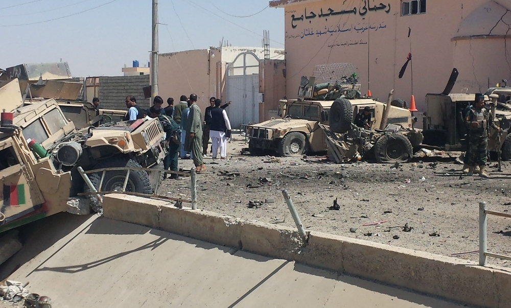 Afghan security personnel inspect the site of a suicide attack near the main police headquarters in Lashkar Gah, capital of Helmand province, on Wednesday. — AFP