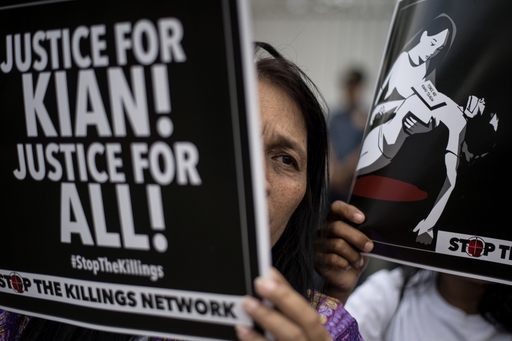 An activist holds a poster against extra-judicial killings during a protest in Manila on Wednesday. — AFP